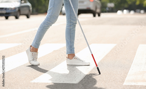 Blind person with long cane crossing road, closeup Wallpaper Mural