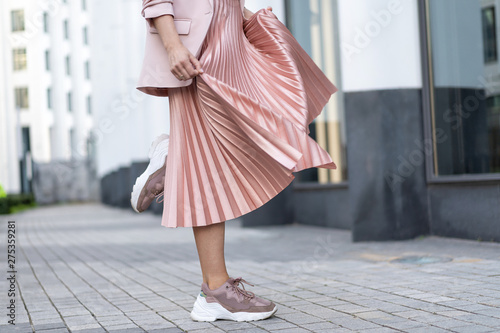 Fotografie, Obraz Pleated skirt coral color and sneakers