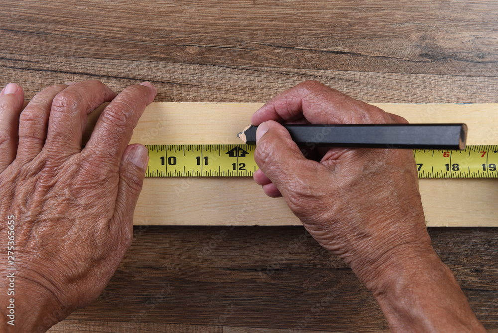 Fototapety, obrazy: High angle closeup of a carpenters hands using a tape measure to mark a cut line on a board