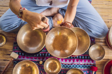 Woman Playing On Tibetan Singing Bowl While Sitting On Yoga Mat Against A Waterfall. Vintage Tonned. Beautiful Girl With Mala Beads Meditating