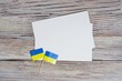 24 August independence Day of Ukraine the concept of the Day of memory of freedom and patriotism. Mini flags with two sheets of white paper on wooden white background. horizontal