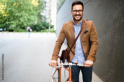 obraz dibond Happy young stylish businessman going to work by bike