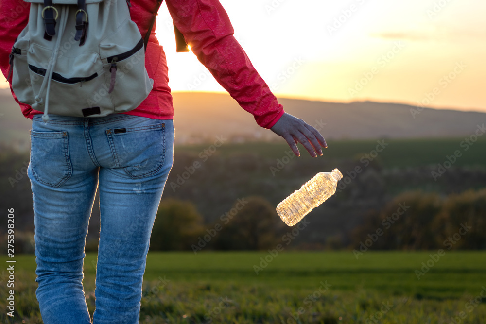 Fototapety, obrazy: Plastic pollution environment. Hiker throwing away plastic bottle in nature.