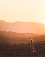 Woman In Mountains At Sunset