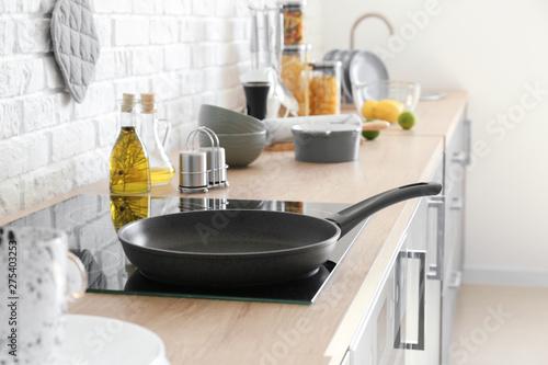 Fototapeta Frying pan on electric stove in kitchen
