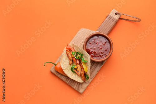 Fototapeta Board with tasty fresh taco and sauce on color background