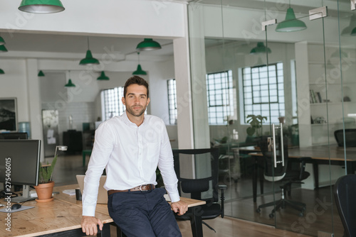 Fotomural  Confident young businessman leaning against an office desk