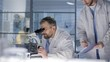 Medium shot of Caucasian male junior researcher, wearing lab coat, coming up to middle-aged project leader, who is looking into microscope, and demonstrating him report sheet with experiment results