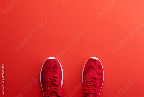 Fotomural  A studio shot of pair of running shoes on red background