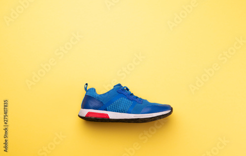 Fotografía A studio shot of running shoe on yellow background. Flat lay.
