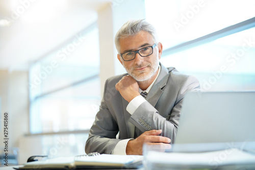 Stampa su Tela  Portrait of mature businessman sitting in office looking at camera