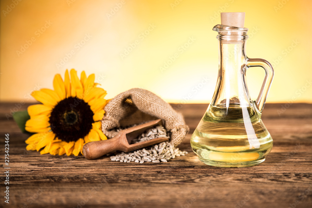 Fototapety, obrazy: Sunflower oil in a bottle and sunflower flowers and sunflower seeds in a sack