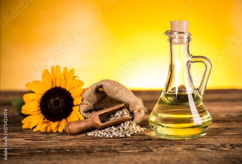 Fototapeta Sunflower oil in a bottle and sunflower flowers and sunflower seeds in a sack obraz