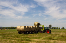Tractor Loading Bales Of Hay Onto A Long Trailer