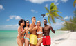 canvas print picture - friendship, summer holidays and vacation concept - group of happy friends taking picture by smartphone on selfie stick and showing thumbs up over tropical beach background in french polynesia