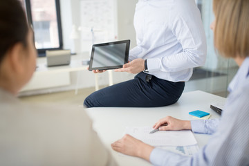 business, people and technology concept - close up of businessman showing tablet computer to colleagues at office