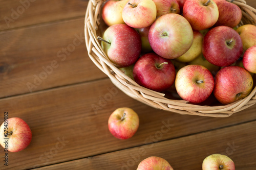 fruits, food and harvest concept - ripe apples in wicker basket on wooden table