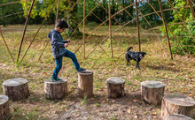 Seven-year-old Boy Playing On Wooden Logs In A Public Park
