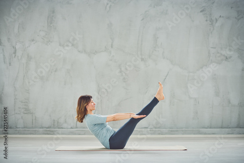 Beautiful Caucasian brunette in blue sportswear sitting on the mat in boat yoga position Wallpaper Mural