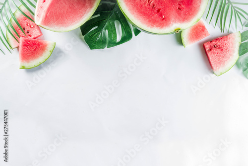 Fototapeta Creative watermelon layout. Summer trendy bright pattern with sliced watermelon and tropical leaves, Above, flatlay with copy space obraz