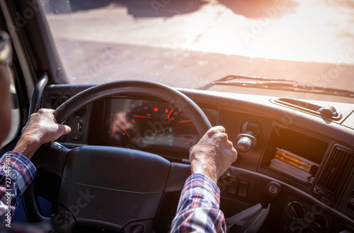 Fotografie, Obraz  Truck driver keeps driving with one hands and change gears,The man Behind Semi Truck Steering Wheel,spot focus