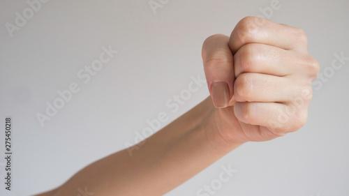 Valokuva  Woman's fist isolated on a light gray background