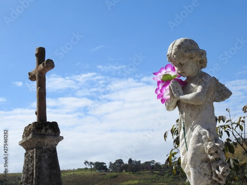 Scene in a cemetery: an old stone statue of a little angel with wings praying Fototapeta