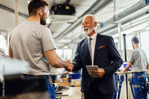Happy mature manager greeting a worker while visiting industrial facility, Canvas Print
