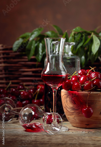 Poster Pays d Europe Cherry liquor and red cherries in a wooden bowl on a wooden table in garden.