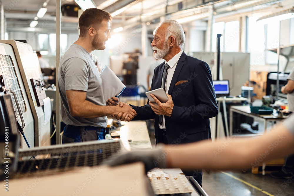 Fototapeta Young manual worker greeting senior manager in industrial building.