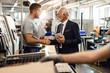 Leinwandbild Motiv Young manual worker greeting senior manager in industrial building.