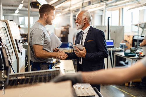 Valokuva  Young manual worker greeting senior manager in industrial building