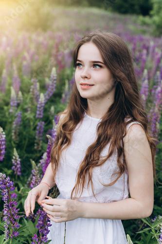 Fototapeta  Portrait of young cute brunette girl in lupine violet field in blossom in summer sunset
