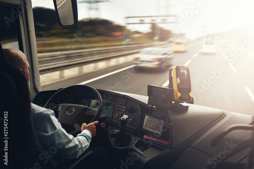 Interior of cab airport transfer bus with driver in motion on fast speed by highway