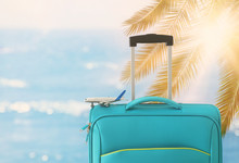 Holidays. Travel Concept. Blue Suitcase And Airplane Toy Infront Of Tropical Background