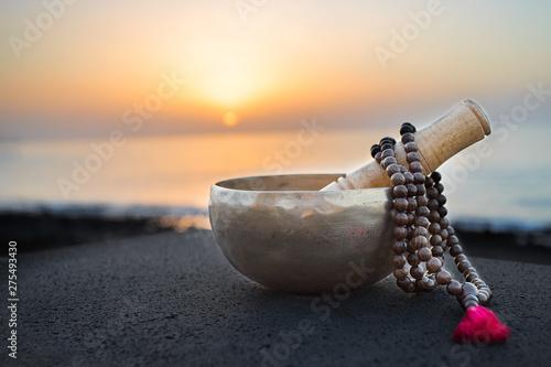 Obraz Tibetan bowl with mala beads on nature seaside background for meditation and mindfulness - fototapety do salonu