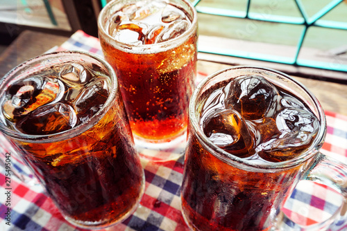 Fotografía  Three glasses of cola with ice on table cloth.