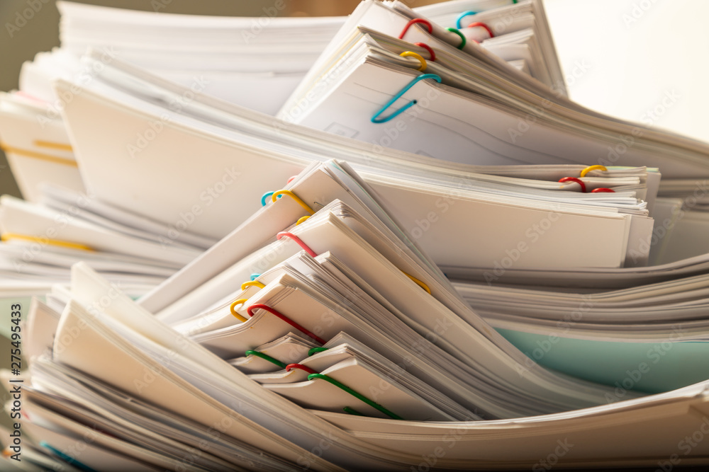 Fototapeta Stack of document paper with colorful paperclip.