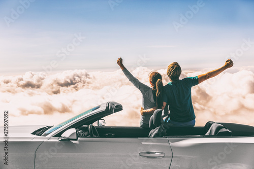 Fototapeta Happy car road trip couple freedom on summer travel vacation driving convertible sports car feeling excited winning free. obraz