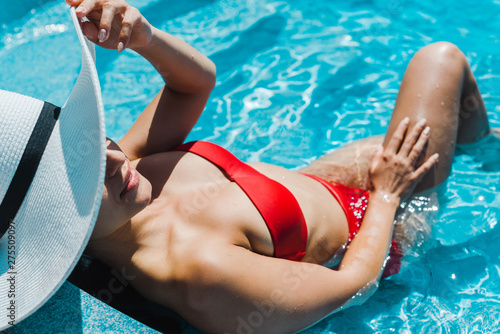 Photo  young woman in stylish straw hat and red swimsuit near swimming pool