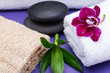 Spa Wellness Concept. Natural Loofah Sponge, rolled up White Towels, stacked Basalt Stones, Bamboo and Orchid Flower on purple background.