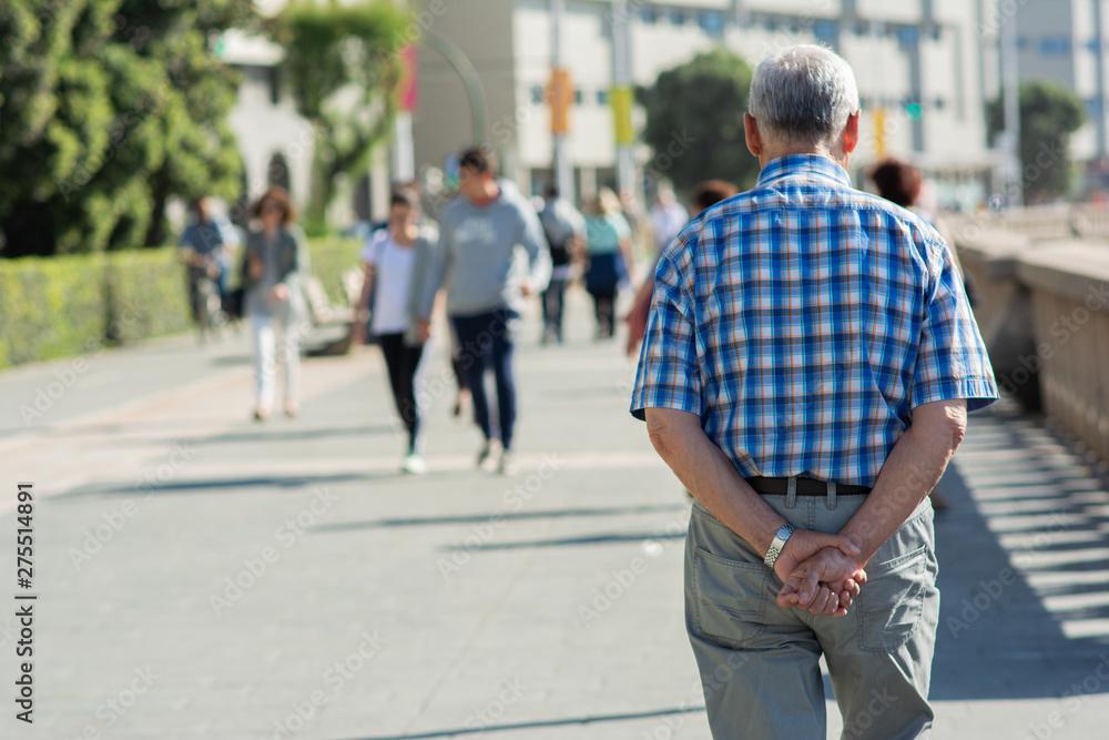 Fototapeta Starszy mężczyzna spaceruje samotnie po mieście