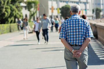 Starszy mężczyzna spaceruje samotnie po mieście