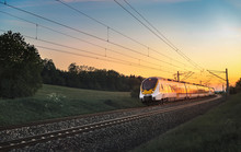 Modern German Train Traveling At Sunset