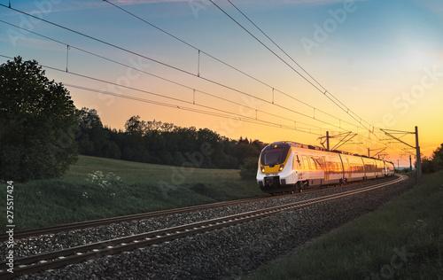 Pinturas sobre lienzo  Modern German train traveling at sunset
