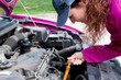 woman in pink cheking the oil of a car