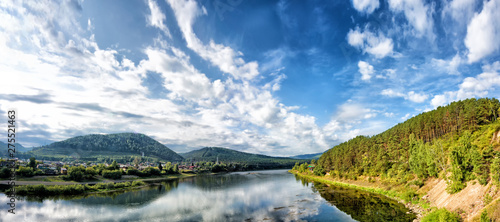 Fototapeta river water on forest mountains background lake and mountain landscape panorama ground view of beautiful autumn nature with rural scenery and settlement reflection in water travel outdoor concept obraz