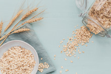Bowl Of Dry Oat Flakes With Ears Of Wheat On Light Background. Cooking Oats Porridge Concept