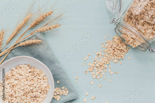 Photo bowl of dry oat flakes with ears of wheat on light background