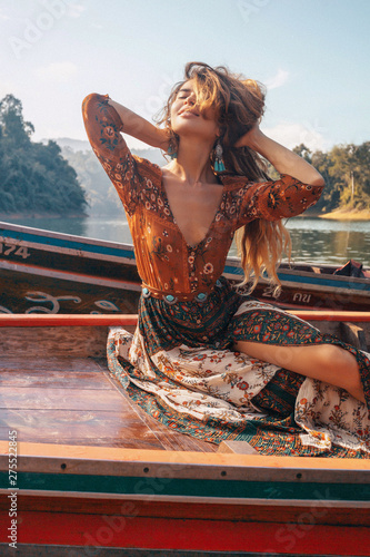 Printed kitchen splashbacks Brown fashionable young model in boho style dress on boat at the lake